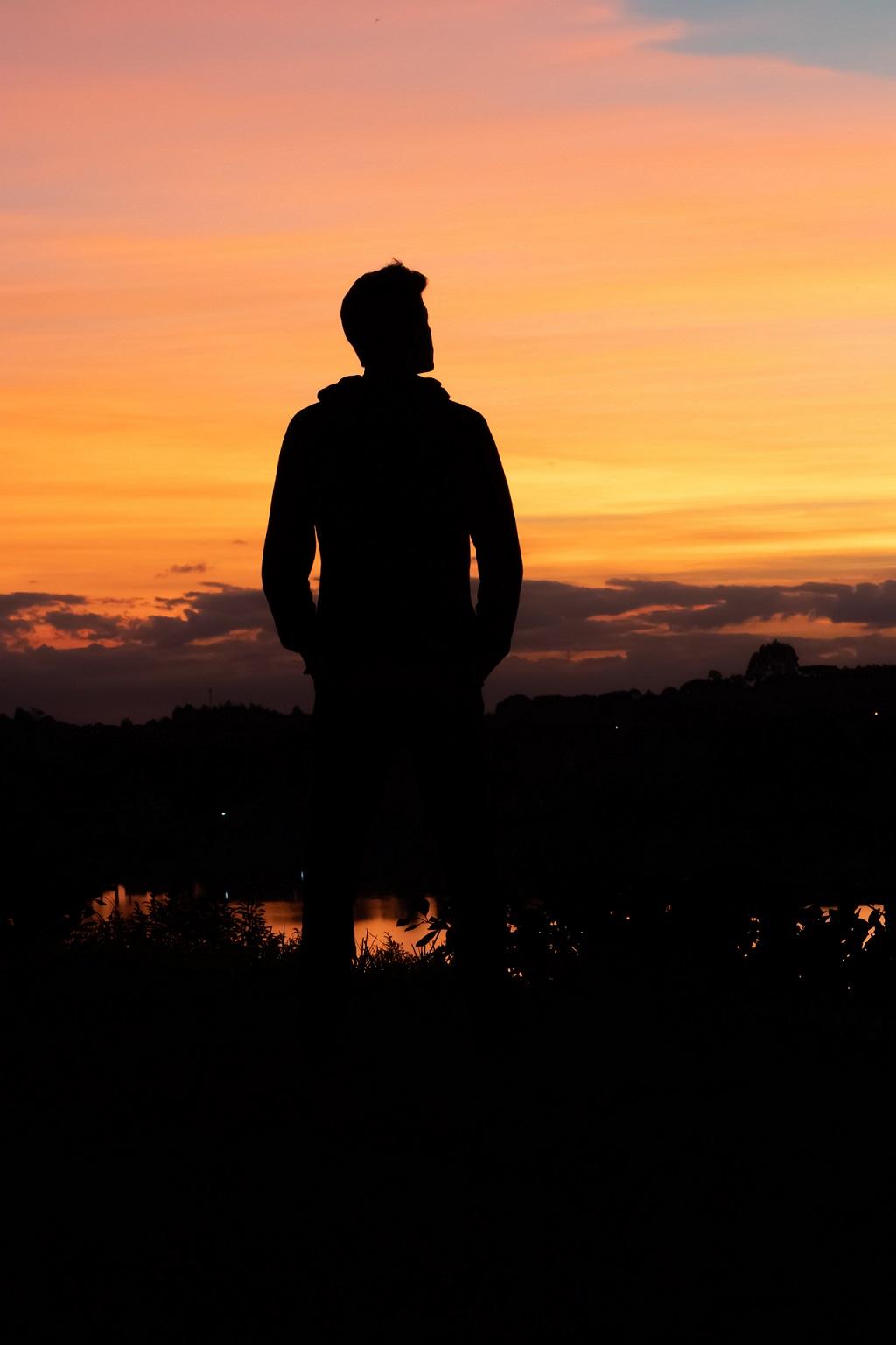 Homme regardant à l'horizon par un couché de soleil